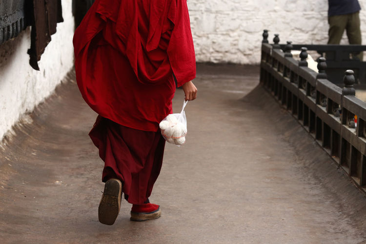 Low Section Of Monk Holding Food On Footpath