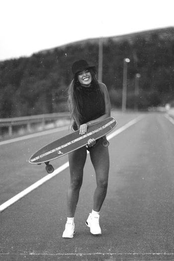Portrait of young woman skateboarding on road