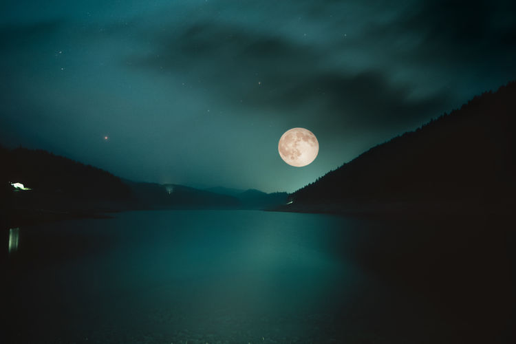 Scenic view of lake by mountains at night