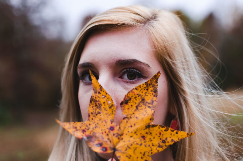 Close-Up Portrait Of Young Woman Holding Autumn Leaf At Forest