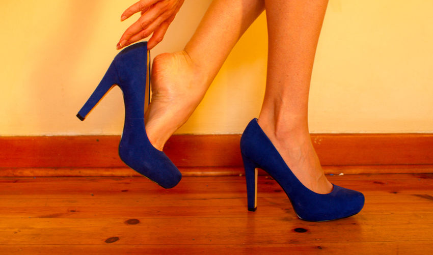 Low section of woman wearing high heels at home