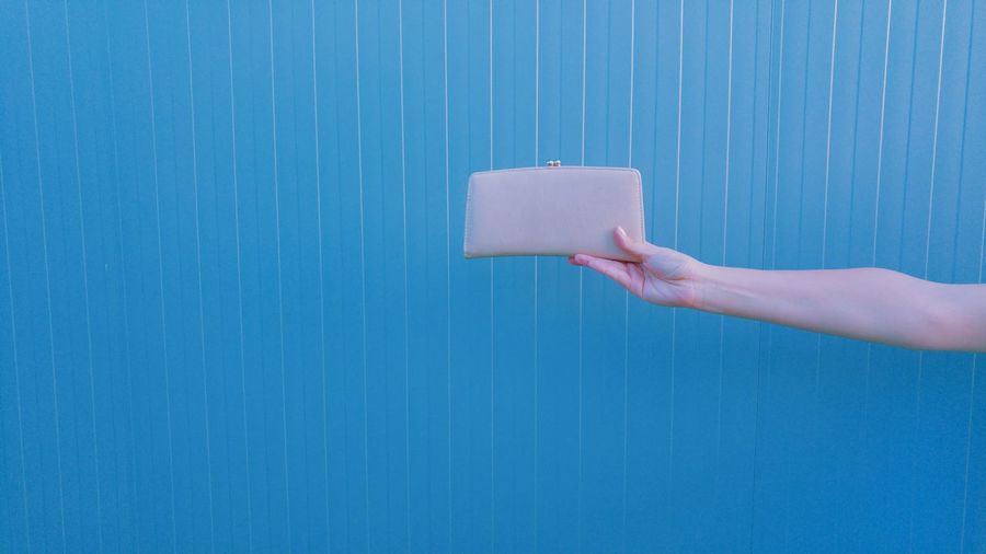Cropped image of hand holding purse against blue wall