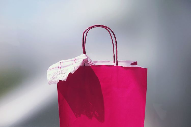 Close-Up View Of Pink Shopping Bag Against Gray Background