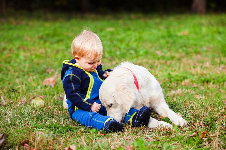 Cute boy sitting with dog on grass