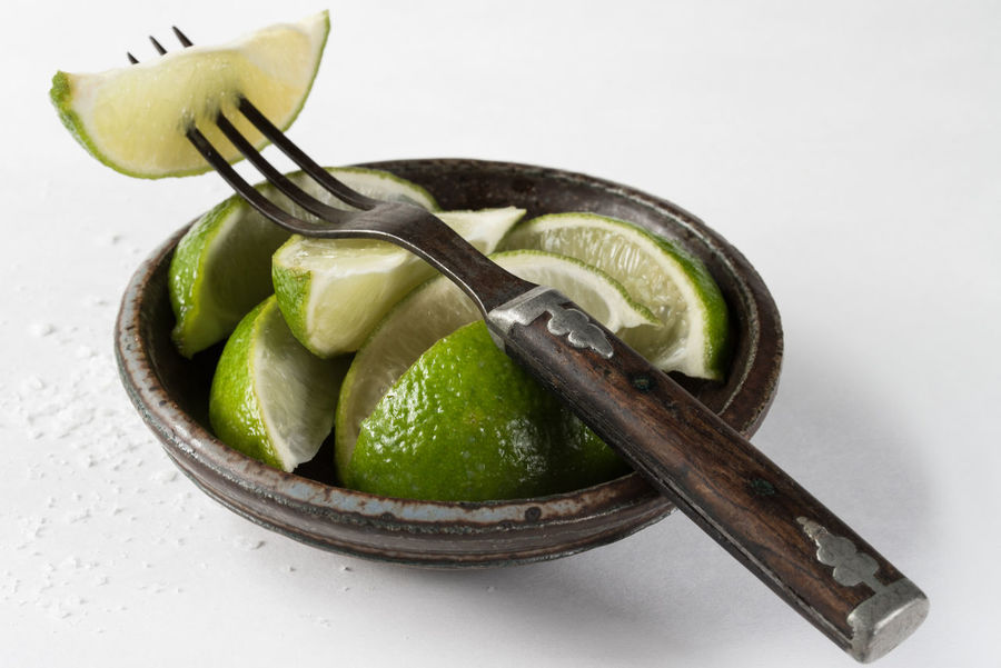 Lime wedges in a pottery bowl Citrus  Cuisine Green Isolated Close Up Fruit Ingredient Lime Pottery Bowl Slices Southwest  Wedges