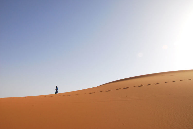 Person walking on sand dune against sky