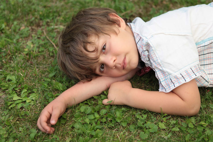 Portrait of cute baby lying on field