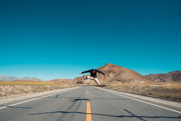 Road trip Desert Nature Real People Blue Sunlight Road Trip Road Outdoors Sign Transportation Mountain Direction Symbol Tibet Clear Sky Climate Marking Copy Space One Person The Way Forward Road Marking Diminishing Perspective Arid Climate Scenics - Nature EyeEm Selects