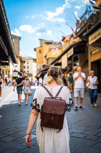 Rear view of women walking on street in city