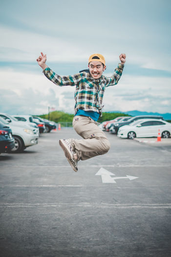 Happy man jumping in parking lot against sky