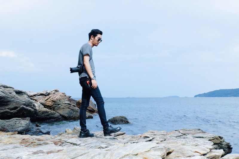 Side view of young man standing on rocky shore