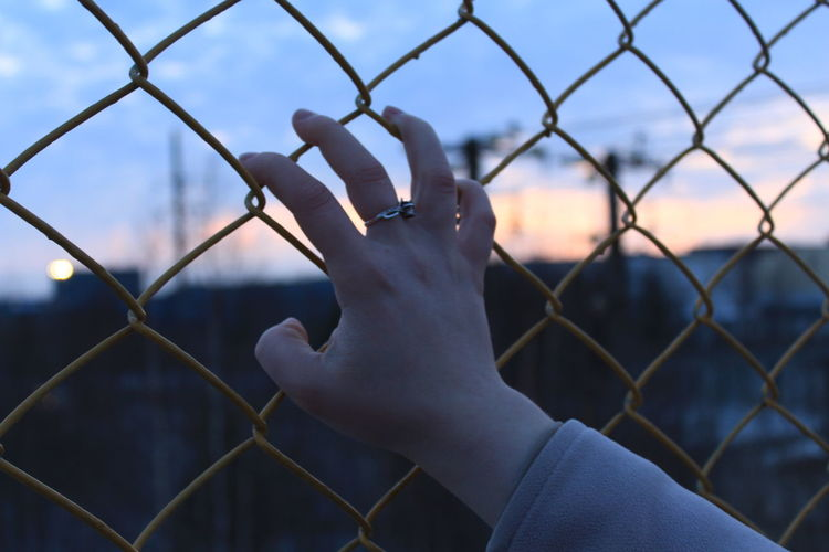 Midsection of person against sky seen through chainlink fence