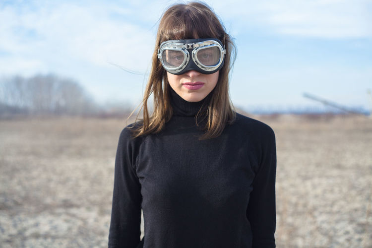 Portrait of young woman wearing swimming goggles while standing on field against sky
