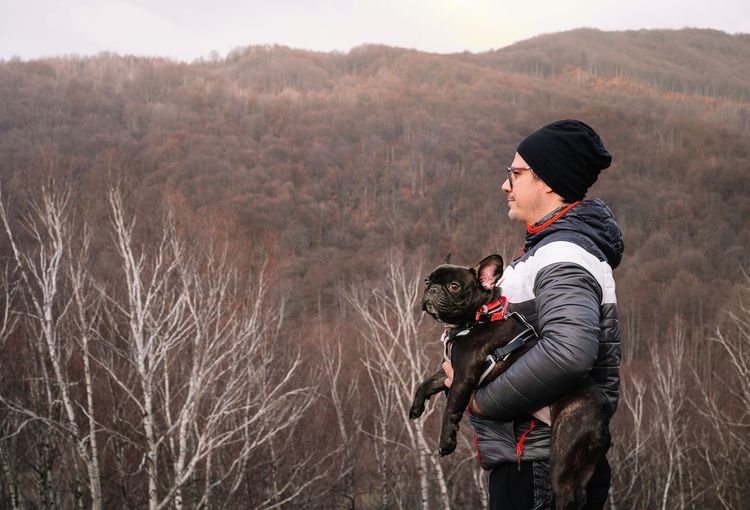 Rear view of man with french bulldog dog on land against winter mountain