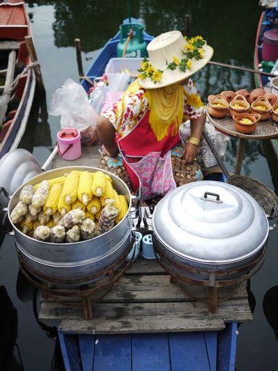 Woman selling corn at damnoen saduak floating market