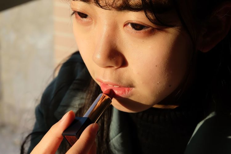 Close-up of girl applying lipstick