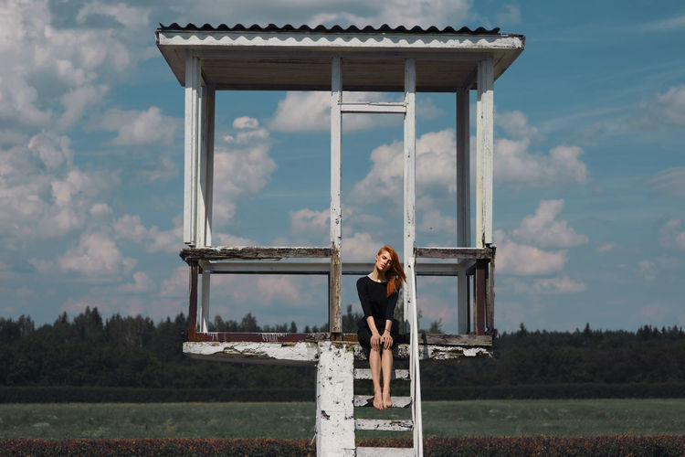 Woman Sitting At Lookout Tower On Field Against Sky