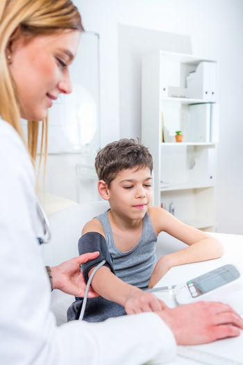 Pediatrician Measuring Boy's Blood Pressure Doctor  Pediatrician Medical Child Boy School Boy Blood Pressure Blood Pressure Gauge Measuring Heart Rate Pulse Medical Test Medicine Human Heart Hospital Clinic Patient Health Kid Stethoscope  Healthcare Care Childhood Female People Exam Professional Examination White Healthy Office Sick Adult Illness Diagnostic Lifestyle Woman Examining Occupation Pediatric Specialist Examine Diagnosis Expertise Indoors  Pediatrist Visit Lab Coat Checking Check Up Two People