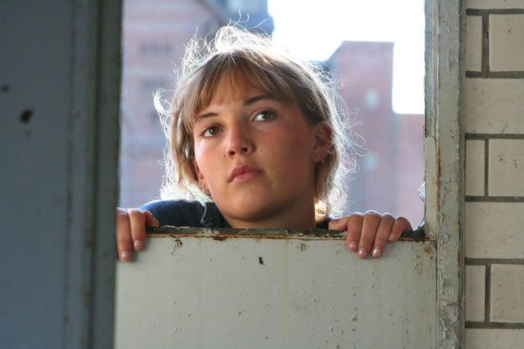 Portrait of girl playing through window