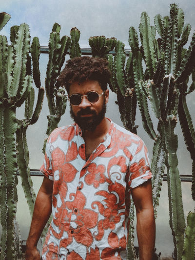 Portrait of man wearing sunglasses standing against cactus
