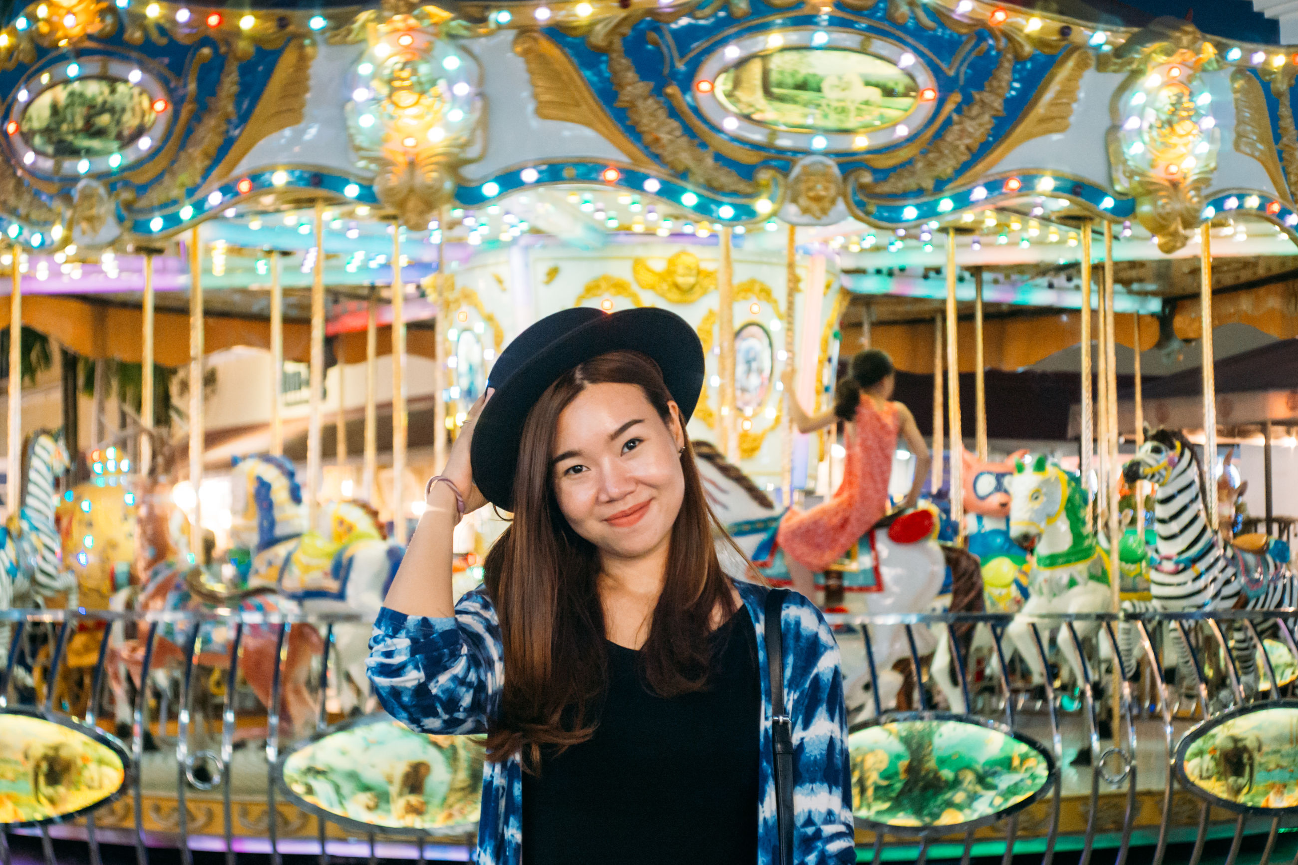 amusement park, leisure activity, one person, young adult, adult, front view, retail, carousel, arts culture and entertainment, amusement park ride, portrait, enjoyment, casual clothing, women, happiness, smiling, waist up, real people, standing, hairstyle, beautiful woman, consumerism