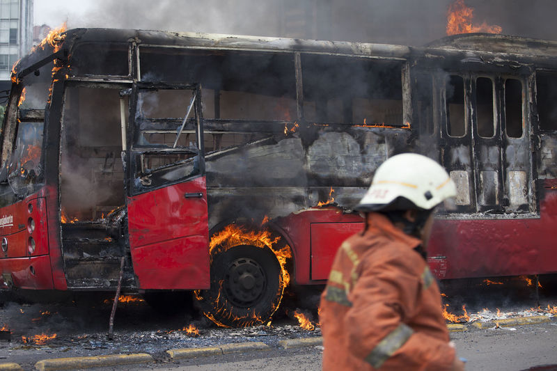 Firefighter Standing By Bus Burning On Street