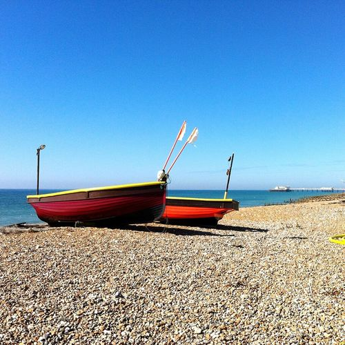 Boats on Worthing beach Beach Sea Sand Nautical Vessel Water Transportation Sunny Tranquility Nature Horizon Over Water Outdoors Day Clear Sky No People Tranquil Scene Moored Blue Red Sky Landscape Nikon D3200 Letsgosomewhere EyEmNewHere Fishing Boat Fishing Industry Tide