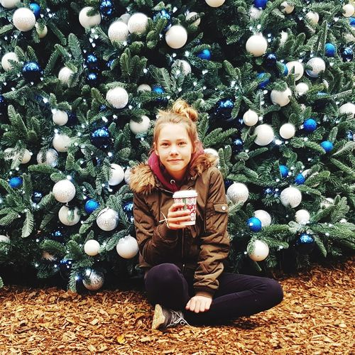 Portrait of girl holding drink while sitting on field against christmas tree
