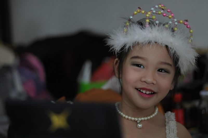 Portrait of smiling girl wearing headdress at home