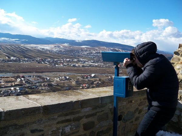 Balcony Binoculars Blue Camera - Photographic Equipment Casual Clothing Cloud - Sky Coin Operated Coin Operated Binoculars Coin-operated Binoculars Holding Looking Through An Object Men Mountain Mountain Range Observation Point Person Scenics Scrutiny Sky Standing Surveillance Technology Tranquil Scene