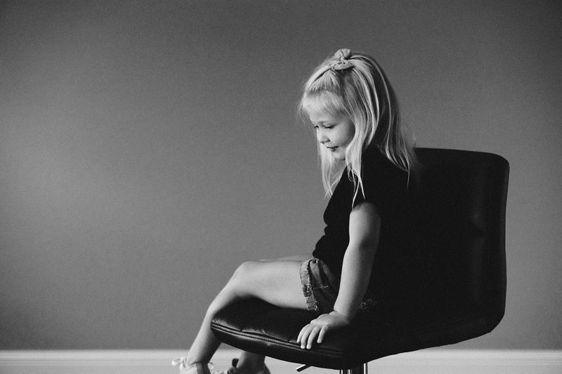 Side view of girl sitting on office chair against wall