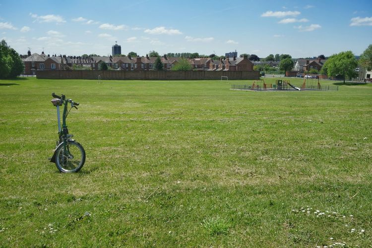 Bicycle parked on grassy field