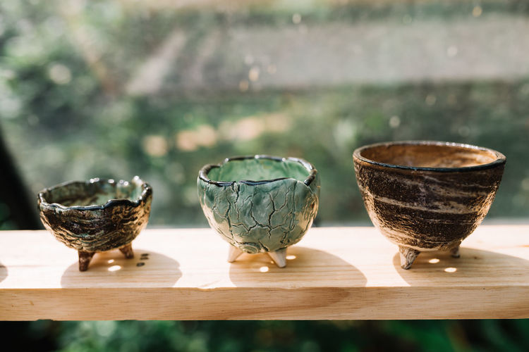 Three Ceramic Pots on a Wooden Shelf ArtWork Cactus Pot Ceramic Ceramic Art Ceramic Design Ceramic Glaze Ceramic Textures Ceramics Close-up Craft Craftsmanship  Cup Japanese Style Mini Pot Natural Texture Pot Potter Showcasing Sunny Texture