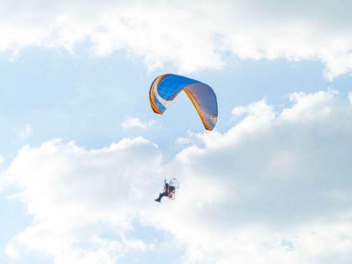 Low angle view of person paragliding against cloudy sky