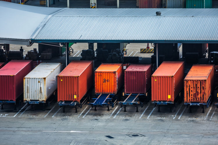 Row of containers against buildings in city