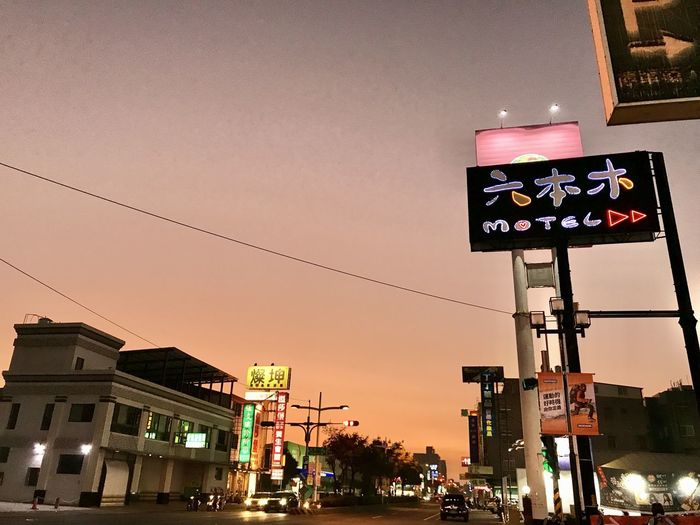 Low angle view of illuminated sign against sky at night