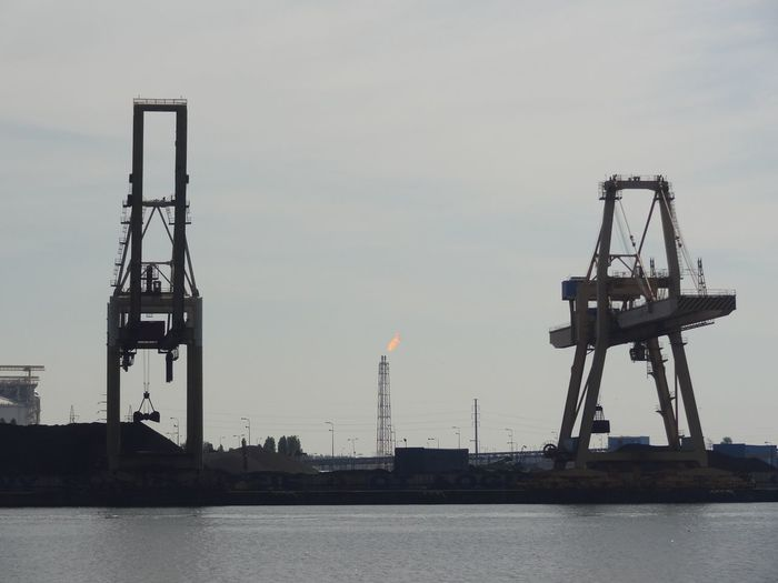 Crane at dock by sea against sky