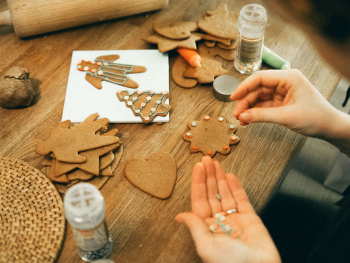 Cropped Hand Decorating Gingerbread Cookies During Christmas