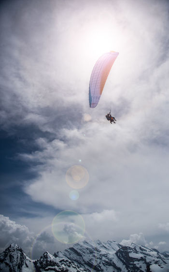 Low angle view of people paragliding against sky on sunny day