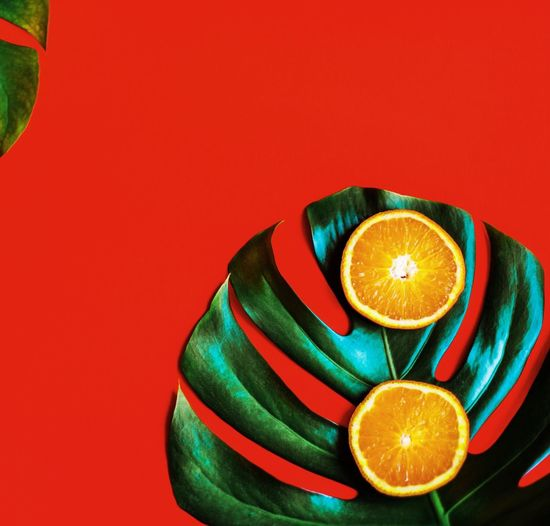 Orange Slices With Leaf On Red Table