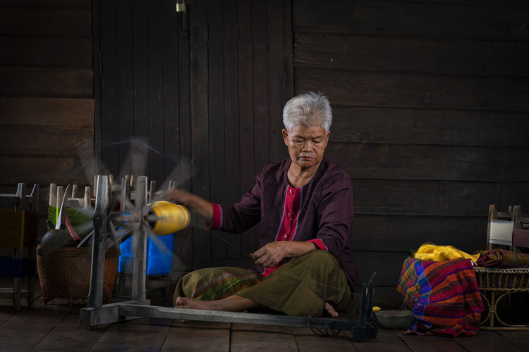 Full length of woman working on hand loom