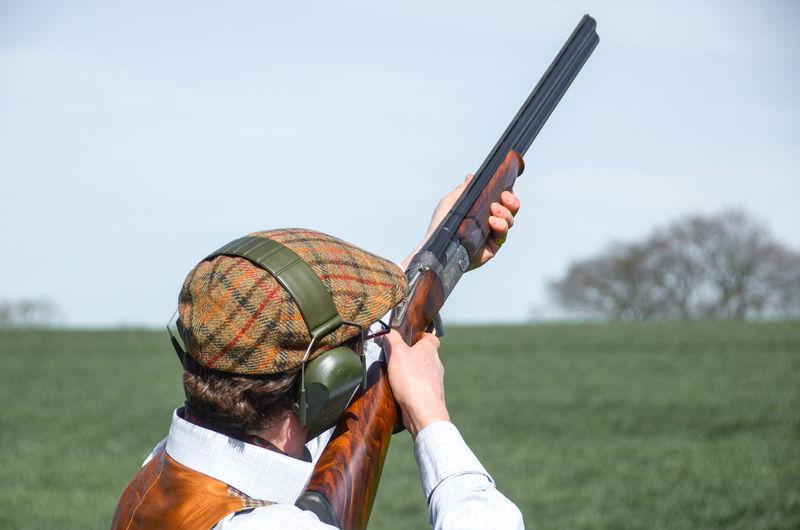 Rear View Of Man Holding Gun On Field