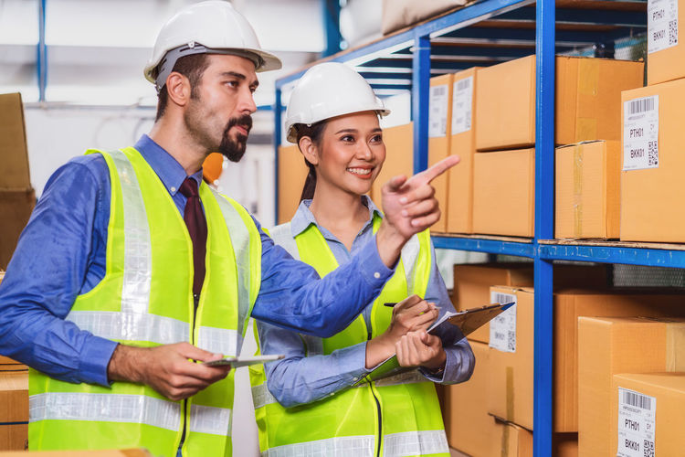 Man pointing at boxes while showing to female coworker in factory