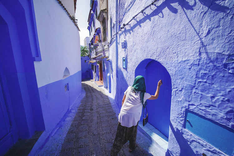 """""""The Blue City"""" We travelled from Sevilla to Tarifa, then took a ferry to Tangier, then a taxi to Chefchaouen, Morocco. EyeEmNewHere a new beginning Chefchaouen Morocco Beauty Blue City Blue Medina Real People Lifestyles Architecture One Person Women Walking Building Footpath Day Digital Nomad Built Structure Leisure Activity Adult Full Length Building Exterior Rear View Standing Outdoors Clothing"""