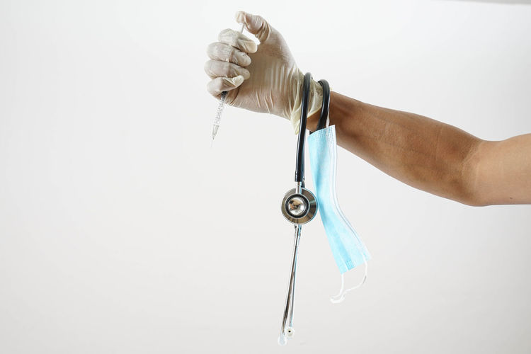 Close-up of hand holding metal against white background