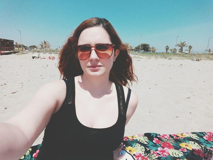 Portrait Of Woman Wearing Sunglasses On Beach