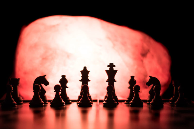 Close-up of silhouette chess pieces in darkroom
