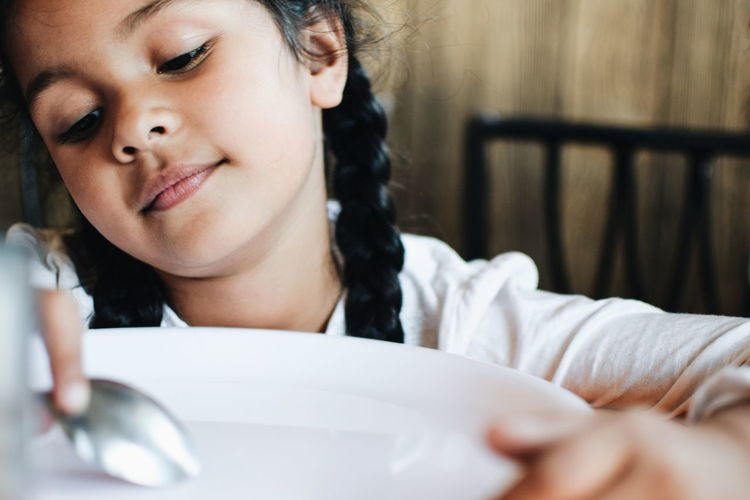 Close-up of girl looking down with spoon and plate at home