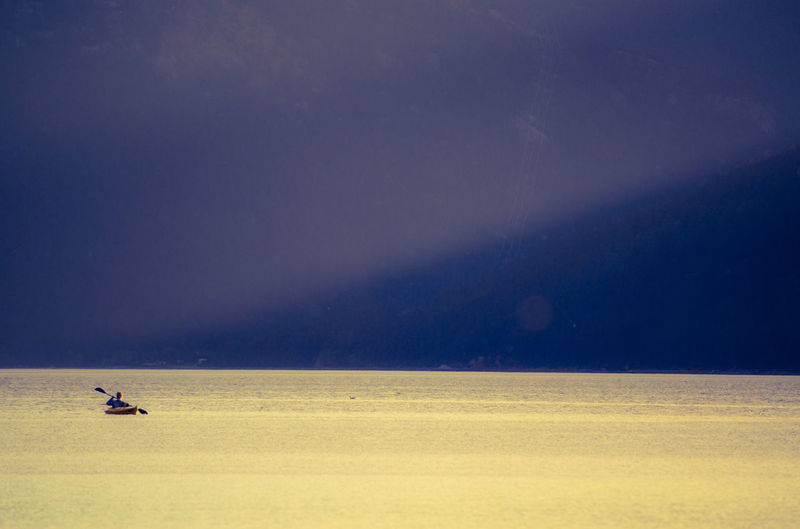 Distant view of person kayaking on sea against sky