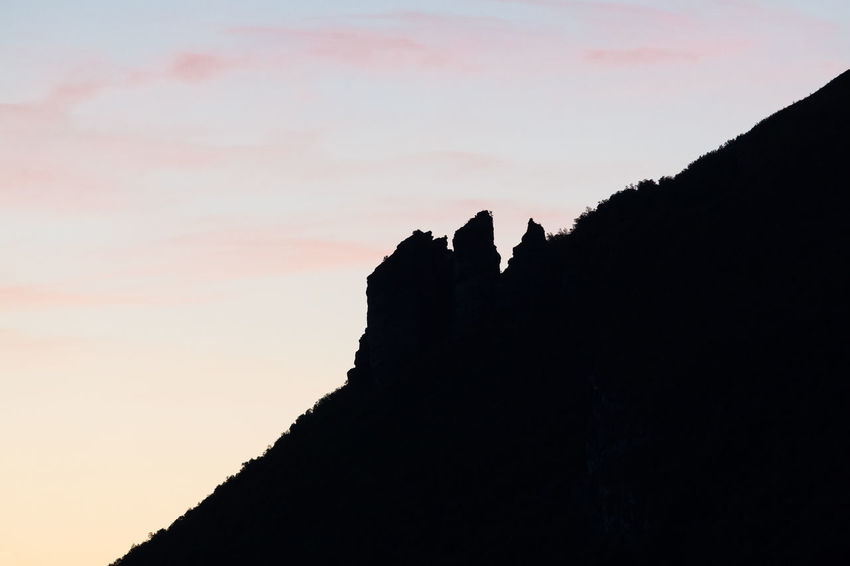 Silhouette of steep rock formation against sky during sunset Copy Space Dramatic Sky Rock Formation Tilt Atmospheric Mood Beauty In Nature Cliff Day Distant Dramatic Landscape Landscape Mountain Mountain Peak Nature No People Outdoors Pastel Colored Pink Color Remote Rock - Object Silhouette Sky Slanted Steep Sunset